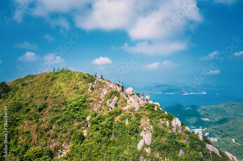 Obraz People walking on Footpath on a sharp mountain in Clear Water Bay, Sai Kung, Hong Kong. Hiking destination, clear weather in Autumn, Epic View - fototapety do salonu
