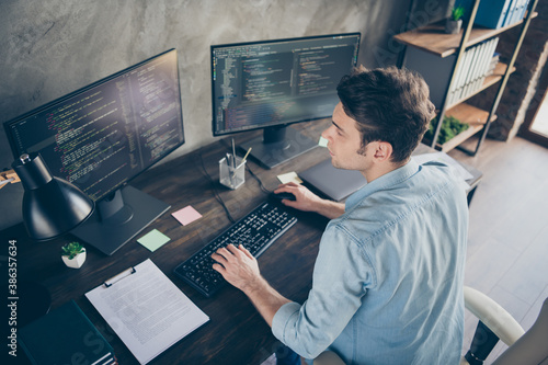 Fototapeta Top above high angle view portrait of his he nice attractive focused skilled geek guy typing bug track report cyberspace security at modern industrial interior style concrete wall work place station obraz