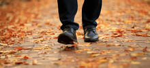 Men Boots Walking On The Sidewalk Strewn With Autumn Leaves