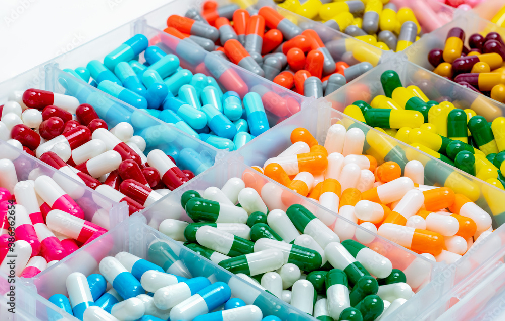 Fototapeta Colorful capsules pill in plastic box.  Pharmaceutical industry. Pharmacy drugstore products. Drug interactions. Healthcare and medicine background. Bright color of capsules pills in plastic tray.