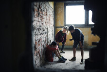 Teenage Boy Attacked By Thugs In Abandoned Building, Gang Violence And Bullying Concept.