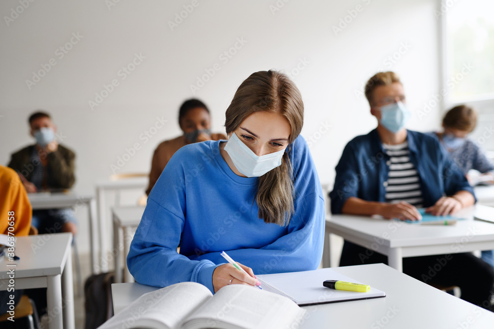 Fototapeta Young students with face masks at desks at college or university, coronavirus concept.