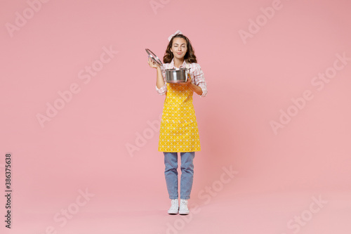 Obraz Full length portrait of smiling young woman housewife in apron hold saucepan with lid feeling food smell while doing housework isolated on pastel pink colour background studio. Housekeeping concept. - fototapety do salonu