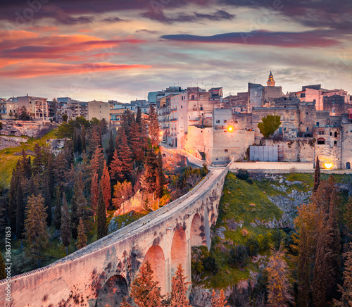 Old viaduct over a deep canyon. Colorful spring sunrise on Gravina in Puglia town. Stunning morning scene of Apulia, Italy, Europe. Traveling concept background.