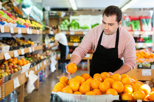 Young happy cheerful positive smiling man in apron selling fresh oranges and fruits on the supermarket