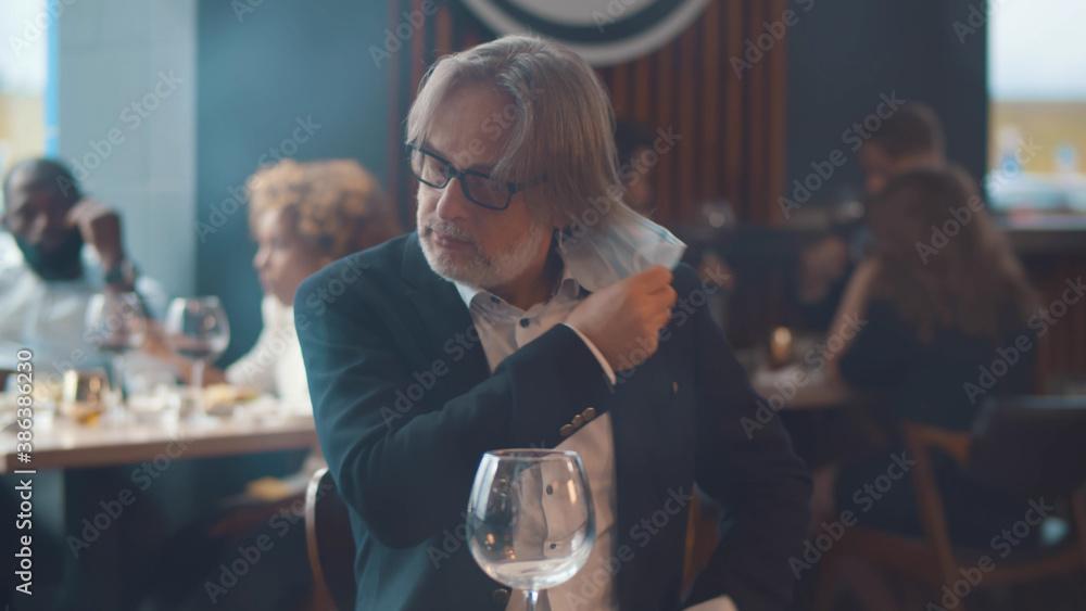 Fototapeta Portrait of senior businessman visiting restaurant putting off safety mask