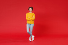 Full Length Of Cheerful Attractive Young Brunette Woman 20s Wearing Basic Casual Yellow Sweater Standing Holding Hands Crossed Looking Camera Isolated On Bright Red Colour Background Studio Portrait.