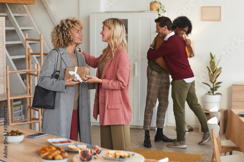 Group of elegant adult people greeting each other and exchanging gifts while wel Fototapet
