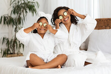 Playful Black Mother And Daughter In Bathrobes Applying Cucumber Pieces To Eyes