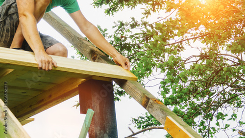 Obraz versatile craftsman working with wood to build a house on a summer day, DIY concept - fototapety do salonu