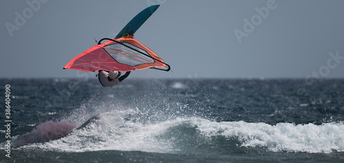 Photo Windsurfer jumping over a big wave balancing in the sky