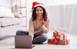 Leinwandbild Motiv Xmas Shopping. Black lady using laptop holding credit card