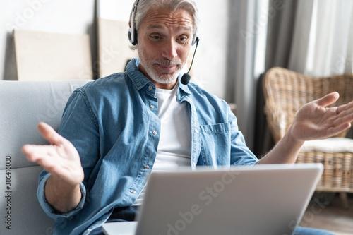 Fototapeta Smiling man in headset watch webinar or training on modern computer, male call c
