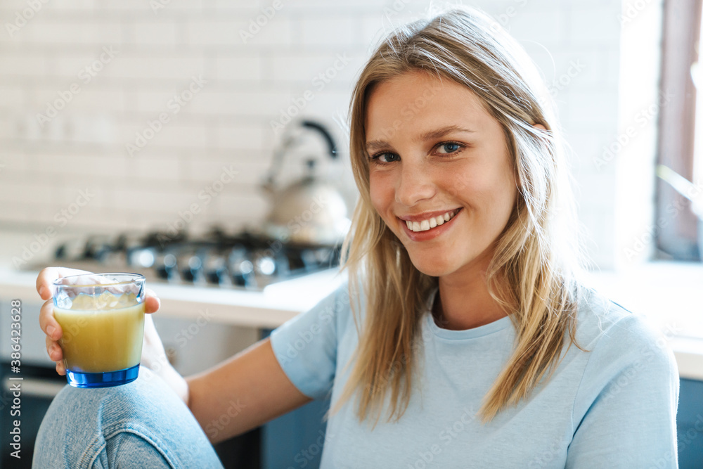 Fototapeta Beautiful joyful girl smiling and drinking juice while having breakfast