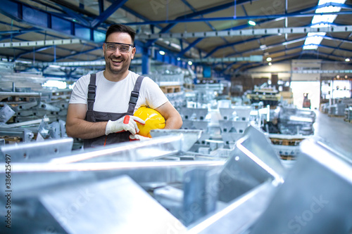 Obraz Portrait of industrial engineer. Smiling factory worker with hard hat standing in factory production line. - fototapety do salonu