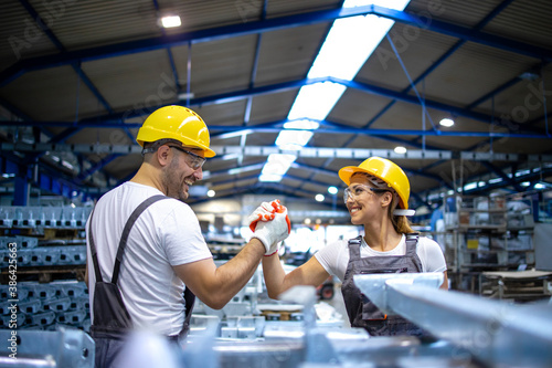 Obraz Factory workers handshaking each other at production line. - fototapety do salonu