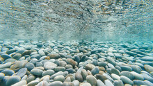 Underwater Photo Of Pebbles On Tropical Beach Reflecting On The Underside Of The Surface Of The Ocean