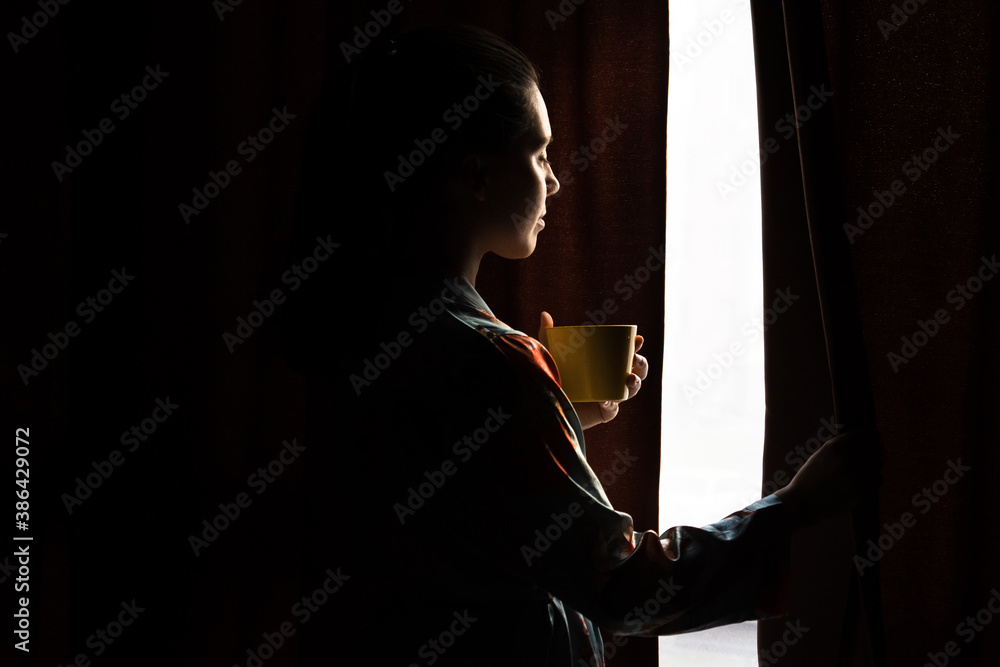 Fototapeta young woman drinking morning coffee looking into window through curtains