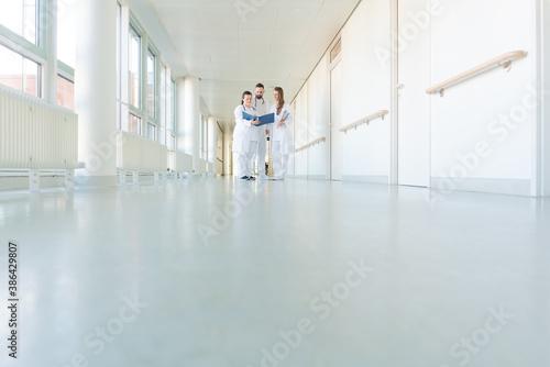 Valokuva Three doctors on hospital corridor having short meeting