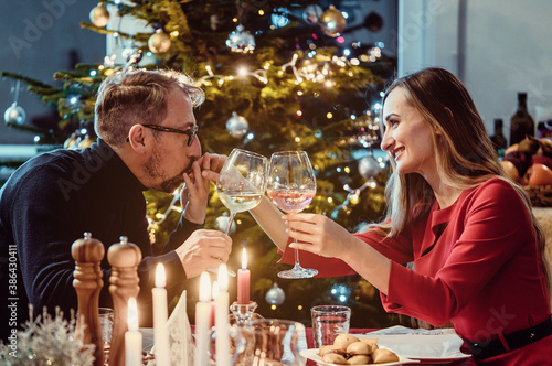 Fototapeta Middle aged couple drinking wine on Christmas eve