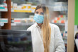 canvas print picture Smiling pharmacist wearing covid coronavirus mask in her pharmacy