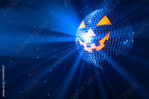 pumpkin disco ball at Halloween party, jack o'lantern with shiny rays in smoke