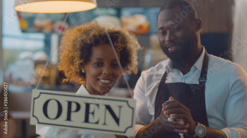 Fototapeta African cheerful small business owners smiling and turning open sign on cafe glass door obraz