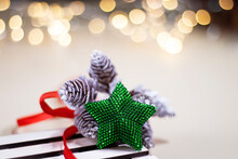 A Green Beaded Star On A Pale Yellow Background And On A Wooden Stand With Bokeh Lights In The Back. Christmas Mood At Home.
