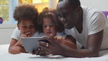 African American Father And Preschool Children Lying Together On Bed And Using Digital Tablet