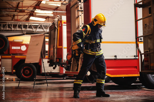 Fotografie, Obraz Full length of brave fireman standing in fire station in full protective uniform and preparing for action