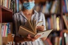 Closeup Of Attractive College Girl Standing In Library With Face Mask On And Reading A Book. Studying During Corona Virus Concept.