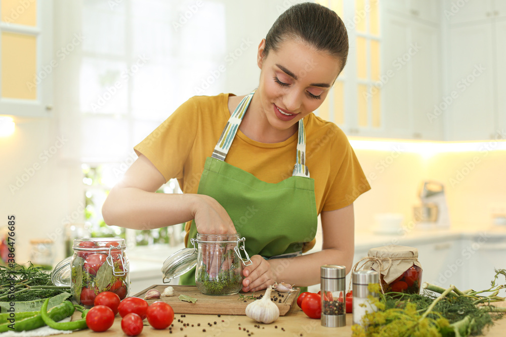 Fototapeta Woman putting dill into pickling jar at table in kitchen