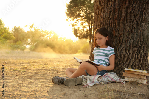 Obraz Cute little girl reading book near tree in park - fototapety do salonu
