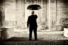 Artistic Creative Image Of Unrecognizable Man In Suit Holding A Umbrella In A Concrete Environment.