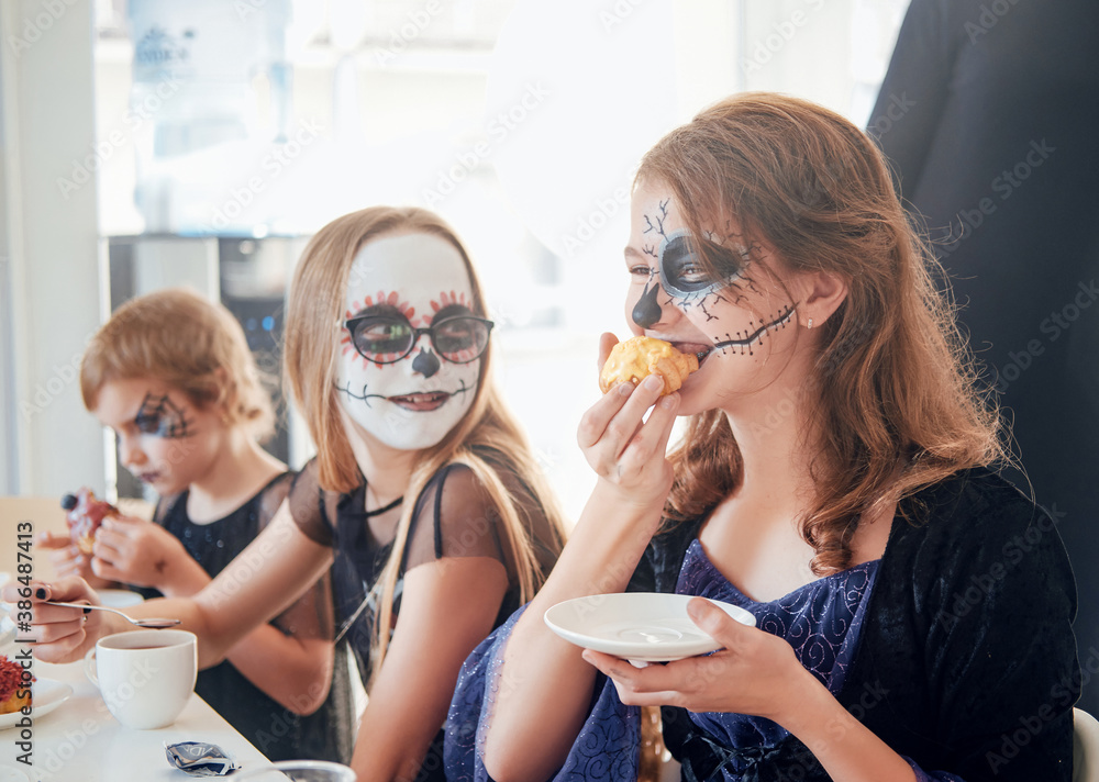 Fototapeta Cheerful preschool girls with costumes eating sweets at masquerade halloween party in illuminated dining room.
