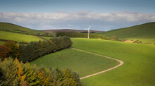A Solitary Wind Turbine In The Lush Green Fields Of Mid Wales UK