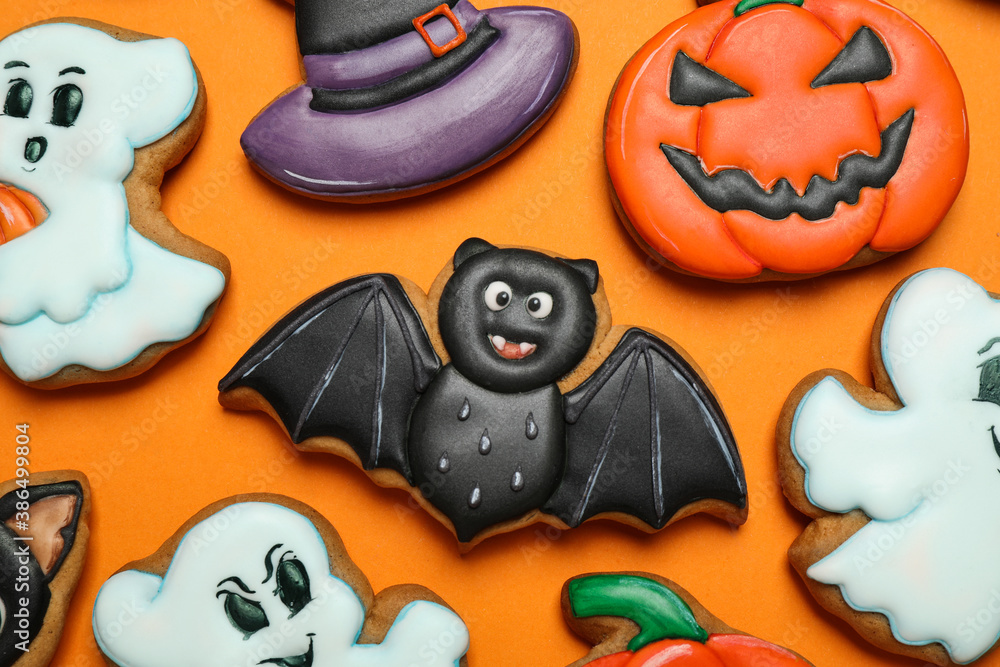 Fototapeta Different decorated gingerbread cookies on orange background, flat lay. Halloween celebration