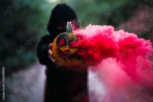 Fotografija Chico joven con mascarilla por covid 19 con calabaza de halloween con humo de co