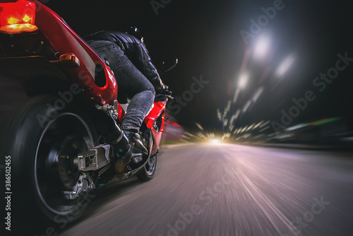 Obraz na plátně Motorbiker is driving a bike on a night road concept.
