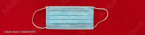 Obraz Corona virus face mask top view with red background panoramic banner. COVID-19 concept. - fototapety do salonu