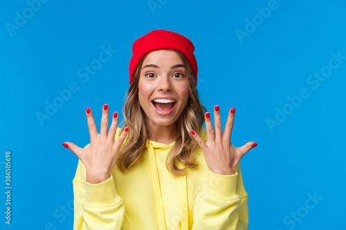Portrait of amused good-looking blonde hipster girl smiling joyfully, explain so Wallpaper Mural