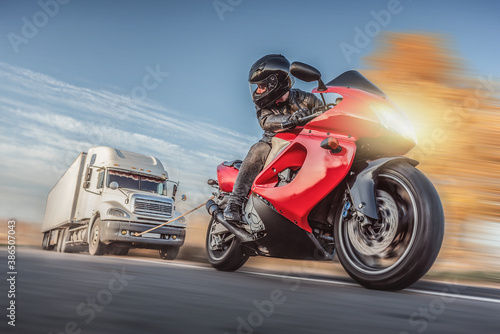 Fotografiet Motorbiker is towing a big truck on the road at high speed concept