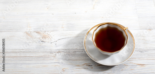 A porcelain cup with tea on a long empty table. Canvas Print