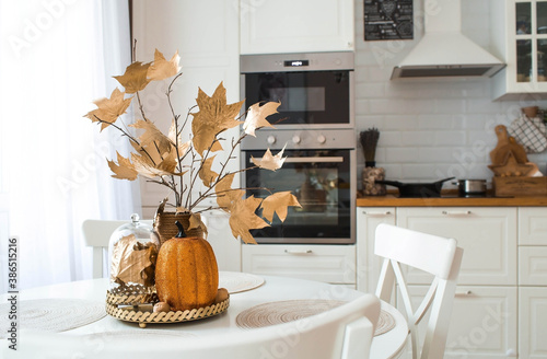 Branches with Golden leaves and a pumpkin on a tray. In the background-the interior of a white kitchen in the Scandinavian style. The concept of home comfort. Autumn decor for the Halloween holiday.