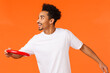 Leinwandbild Motiv Happy, joyful charismatic african-american man playing with friends, throwing red frisbee left and smiling, spending time outdoors in park, having picnic, vacation over orange background