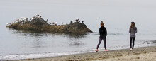 Pair Of Young Women Walking At Deception Pass