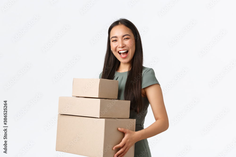 Fototapeta Small business owners, startup and work from home concept. Smiling successful businesswoman, shop manager packaging boxes for shipping to clients, carry items for delivery, white background