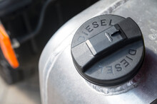 """Black Plastic Cap Of Aluminum Gas Tank In Silver Color With The Inscription """"DIESEL"""". The Fuel Tank Of The Truck Is Closed With A Cap. The Concept Of Rising Fuel Prices In The World."""