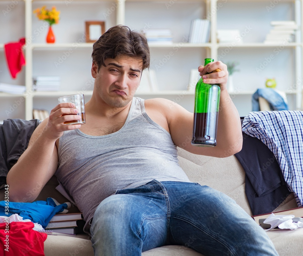 Fototapeta The young man student drunk drinking alcohol in a messy room