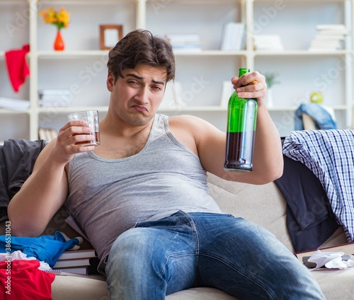 The young man student drunk drinking alcohol in a messy room